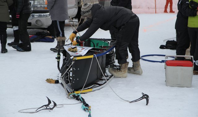 While the fans celebrate mushing, Pete works on his sled.